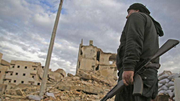 Een strijder van Levant Front kijkt uit over een verwoeste stad Beeld afp