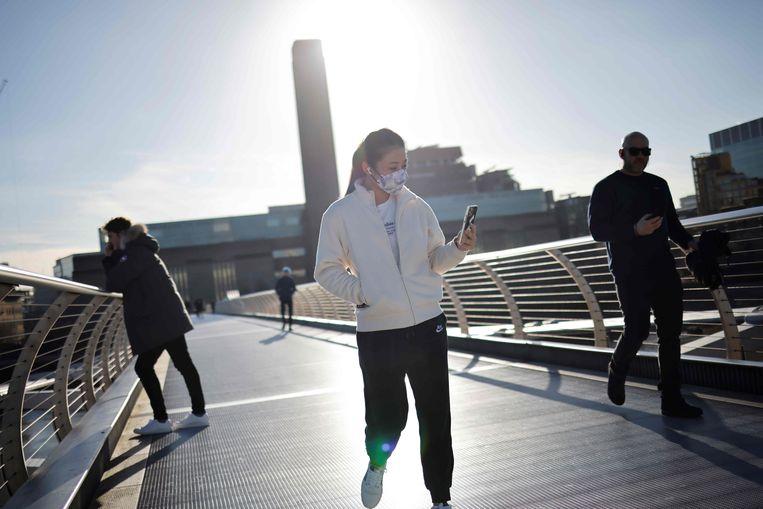Mensen wandelen over de Millenniumbrug in Londen, Verenigd Koninkrijk, waar inmiddels de derde nationale lockdown is ingegaan. Beeld AFP
