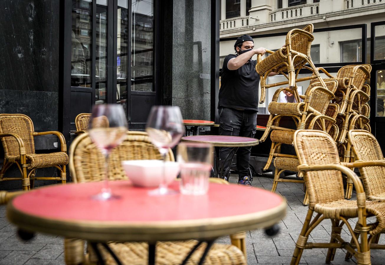 Een horecaondernemer ruimt 0 18 uur zijn terras weer op in Amsterdam.