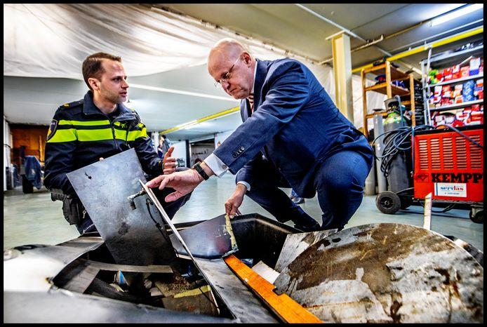 Minister Grapperhaus bezoekt een garage in Soest waar aan auto's gesleuteld wordt om geld  en drugs in te verbergen. Een agent geeft uitleg.
