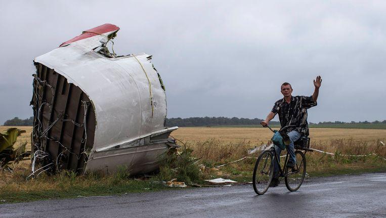 Een man fietst langs een groot brokstuk van de neergehaalde MH17. Beeld REUTERS