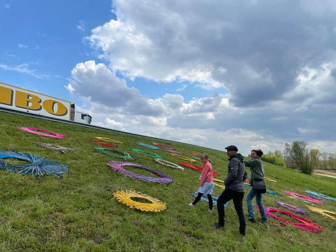 Buurtbewoners nemen een kijkje bij de 'pop-up kunst' op het talud naast de A50.