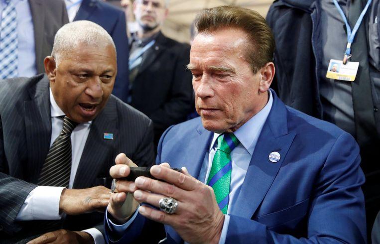 Arnold Schwarzenegger en Frank Bainimarama, de president van Fiji, drinken kava op de voorbije klimaatconferentie. Beeld REUTERS