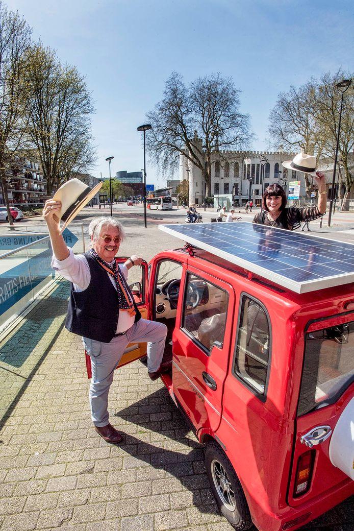 Mario de Kort en zijn vrouw Cecile tonen hun wagentje op zonnepanelen, staand voor het Tilburgse stadhuis.