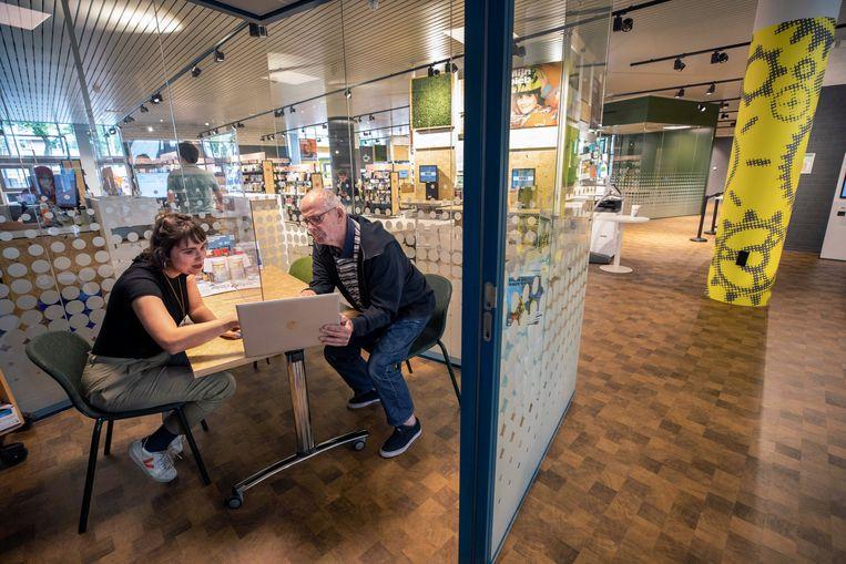 Bibliotheekmedewerker Lola de Koning helpt de 81-jarige Ab Rosbag bij het aanvragen van een coronatoegangsbewijs op papier.  Beeld Werry Crone