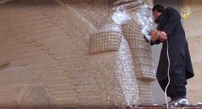 Een IS-militant vernielt een eeuwenoud beeldhouwwerk. Beeld PHOTO_NEWS