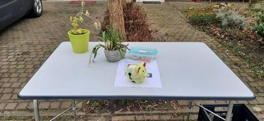 Dit tafeltje wordt iedere dag buiten gezet voor het huis van Janna Markestein in Welberg. Voorbijgangers kunnen een armbandje kopen en lege flessen achterlaten. betalen kan via een QR-code of contant in de spaarvarken.