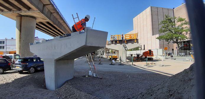 Komt dat zien! Gehelmde bouwvakkers toveren zomaar een afrit voor de bus uit de grond. Onder de metrobaan door. Eind dit jaar is de klus geklaard.