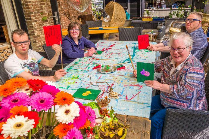 In het Thomashuis in Nieuwkuijk worden plankjes beschilderd voor ouderen uit de buurt die ze voor het raam kunnen zetten, ene kant rood andere kant groen. Vlnr. Ardy, Saskia, Annemiek en Jan.