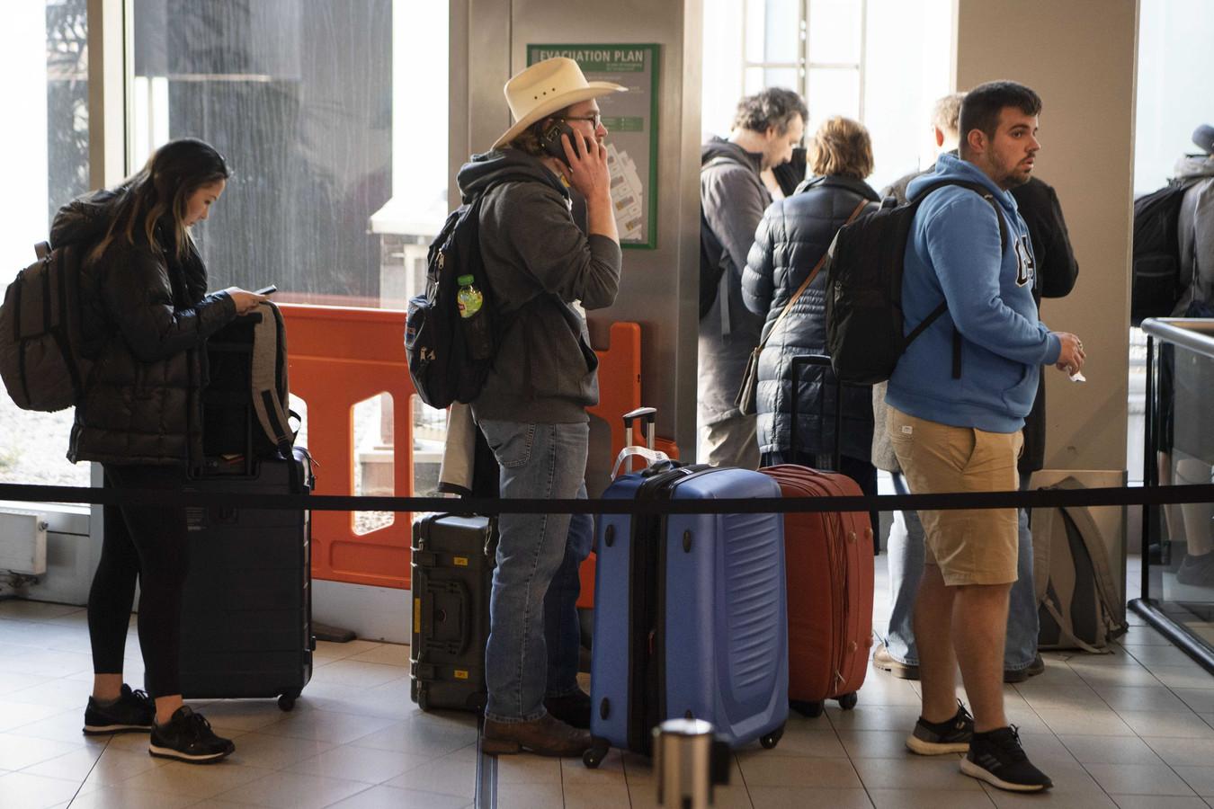 Drukte in de vertrekhal bij de informatiebalie van KLM op Schiphol.