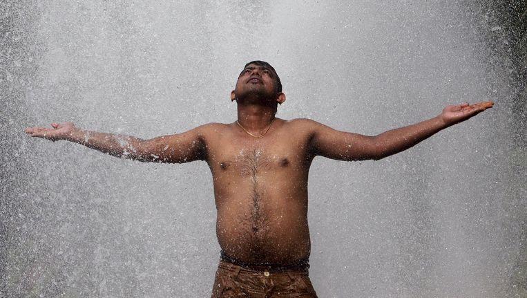 Een man zoekt verkoeling op bij een gemeentelijke waterzuiveringsinstallatie tijdens een hete zomerdag in Agartala, India. Beeld reuters