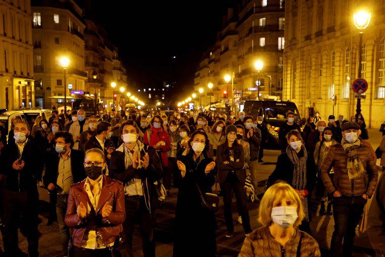 Een menigte applaudisseert tijdens de nationale hommage in de Sorbonne voor de vermoorde docent Samuel Paty. Ze volgen de plechtigheid, waarop president Macron sprak, buiten op een groot scherm.    Beeld Ludovic MARIN / AFP