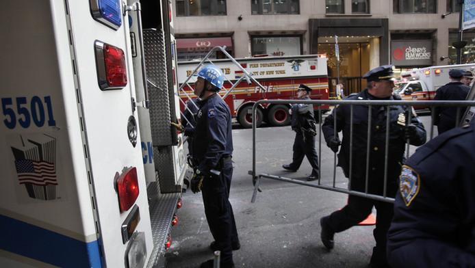 Reddingsmedewerkers verzamelen zich buiten het gebouw waar de vrouw in een lift bekneld is geraakt.