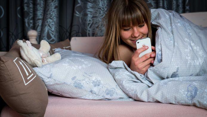 Archiefbeeld ter illustratie: Een meisje chat via whatsapp terwijl ze in bed ligt.