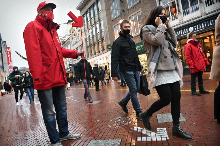 Een medewerker van de gemeente Eindhoven staat met een pijl aan het begin van de winkelstraat om mensen te wijzen op de juiste looprichting. Beeld Marcel van den Bergh / de Volkskrant