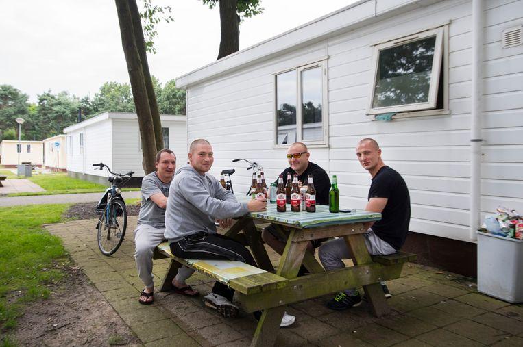 Poolse arbeidsmigranten bij hun woning op een recreatiepark in Oss. Beeld ANP