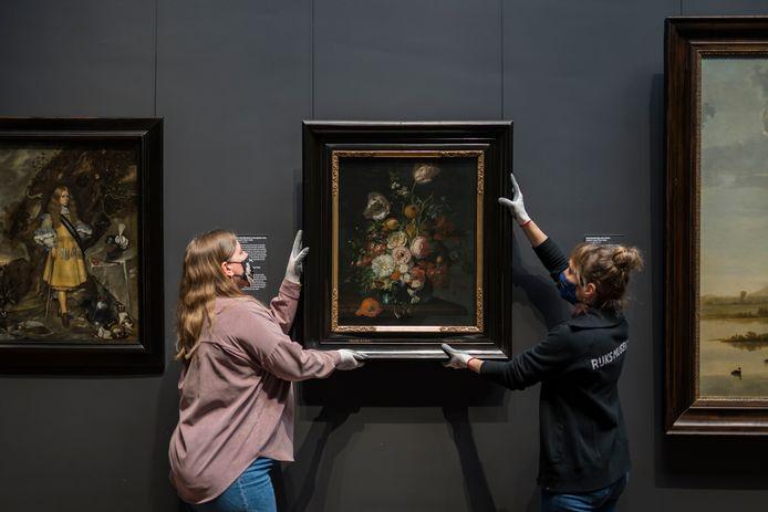Het werk 'Stilleven met bloemen' van Rachel Ruys (ca. 1690/1720) wordt opgehangen in het Rijksmuseum.