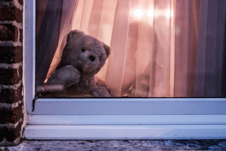 Een knuffelbeer achter een raam in Antwerpen. 'Berenjachten' moesten wandelingen voor kindjes opleuken. De oproep kreeg veel respons. Beeld BOB VAN MOL
