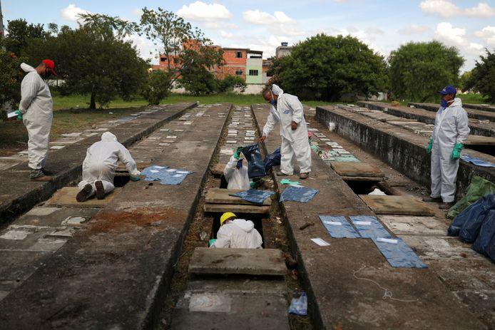 Stadsarbeiders in beschermende pakken moeten oude graven leegmaken om plaats te maken voor nieuwe overledenen.