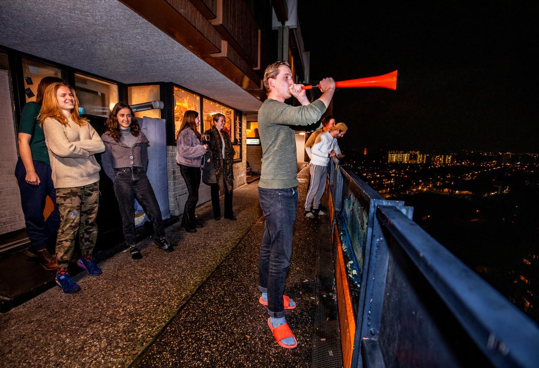 Utrechtse studenten luiden de avondklok om 21.00 in met een vuvuzela. Beeld Raymond Rutting / De Volkskrant