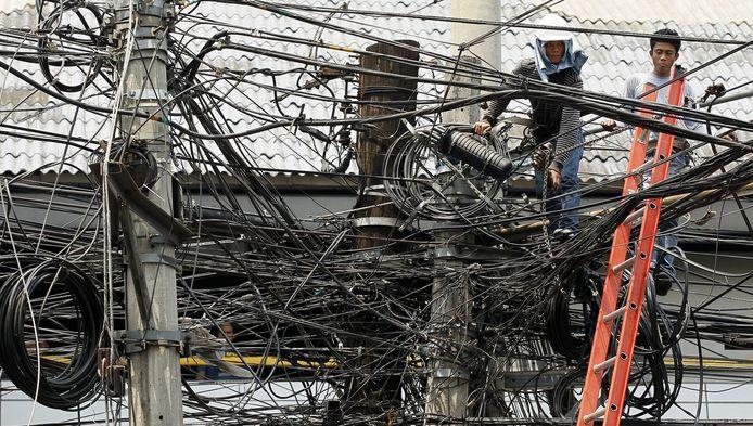 Een Filipijnse arbeider bezig met de herstelwerkzaamheden van een elektriciteitsleiding.
