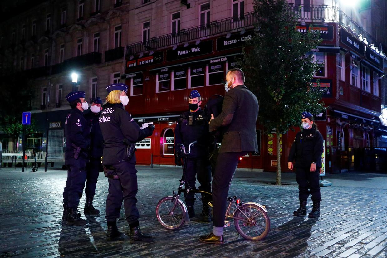 Politieagenten controleren een fietsende man in Brussel. In de hoofdstad geldt nog steeds een avondklok vanaf 22 uur.