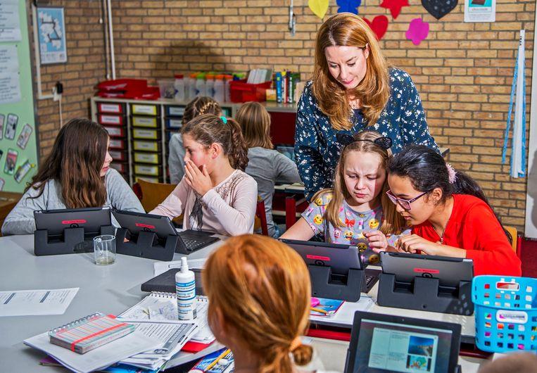 Basisschool De Brandaris in Hellevoetsluis werkt met tablets en niet meer met boeken. Ook de docenten kijken digitaal na. Beeld Hollandse Hoogte / Frank de Roo