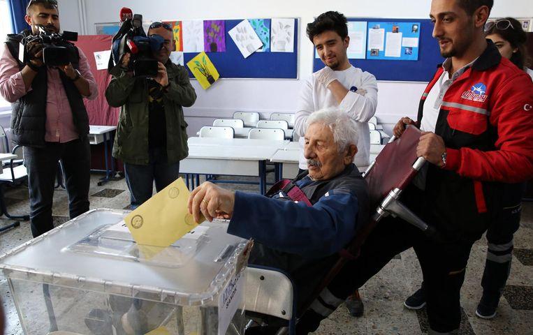 Verzorgers helpen een oudere meneer in een rolstoel bij het uitbrengen van zijn stem, Ankara, 16 april. Beeld getty