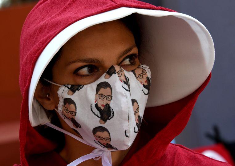 In Hand Maid's Tale-outfit en met een mondkapje met afbeeldingen van opperrechter Ruth Bader Ginsburg neemt deze vrouw deel aan een Women's March in Los Angeles, eerder deze maand.  Beeld Keith Birmingham / Getty