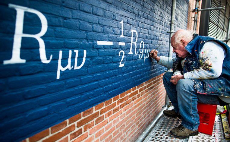 Schilder Jan Willem zet een formule van Einstein op de muur van Museum Boerhaave in Leiden. Beeld null