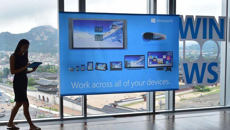 Een vrouw bij een advertentie voor besturingssysteem Windows 10. Beeld AFP
