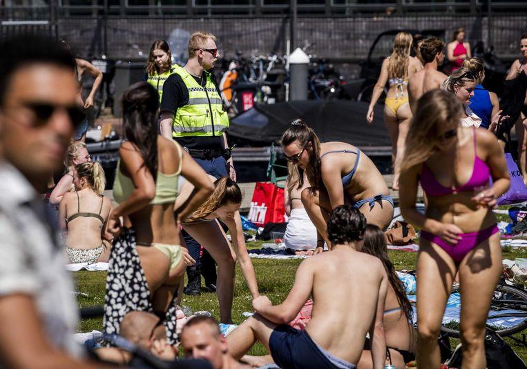 Handhavers en politie ontruimden het Amsterdamse Park Somerlust vanwege de te grote drukte op Hemelvaartsdag. Hoewel de horeca nog dicht was vanwege de coronamaatregelen gingen veel mensen naar buiten.  Beeld ANP