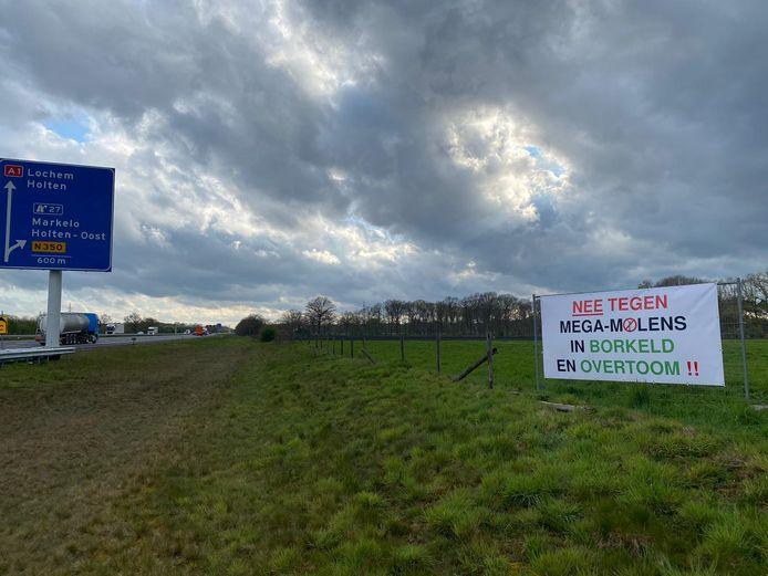Spandoek tegen windmolens langs de A1 bij Rijssen.