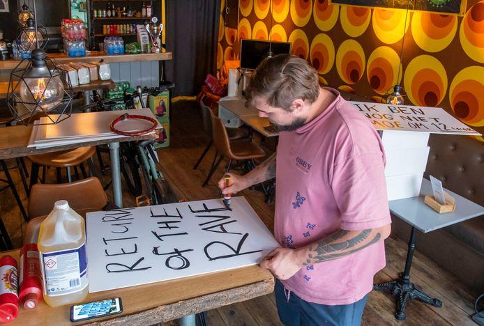 Jort Brink maakt enkele protestborden klaar voor de demonstratie Unmute Us zaterdag in Harderwijk. Dat het landelijke protest navolging krijgt in Harderwijk, is een initiatief van de restauranteigenaar.