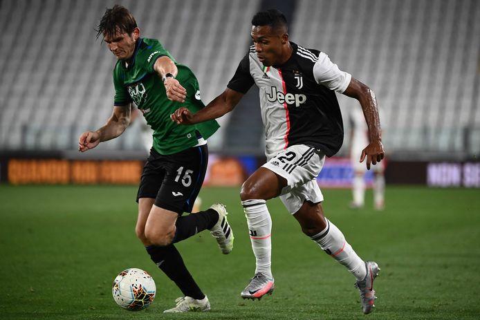 Marten de Roon van Atalanta neemt het in zijn groene shirt op tegen Alex Sandro van Juventus.