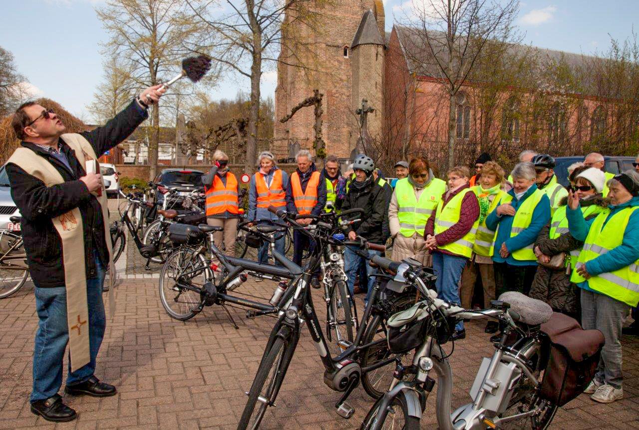 Priester Luc Frenay zegent de fietsen van Okra Varsenare.