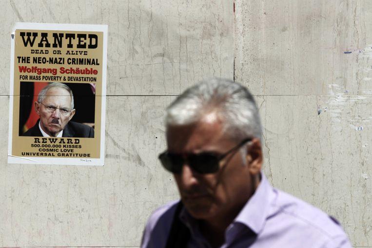 Een man loopt langs een poster van de Duitse minister van Financiën Schäuble. Beeld AP