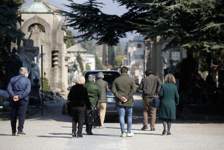 Nabestaanden lopen achter een rouwauto in het centrum van Bergamo. Beeld AP
