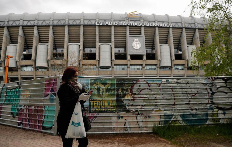Een vrouw met mondkapje wandelt voorbij het Bernabéu-stadion van Real Madrid, dat momenteel een upgrade krijgt. Beeld Anadolu Agency via Getty Images