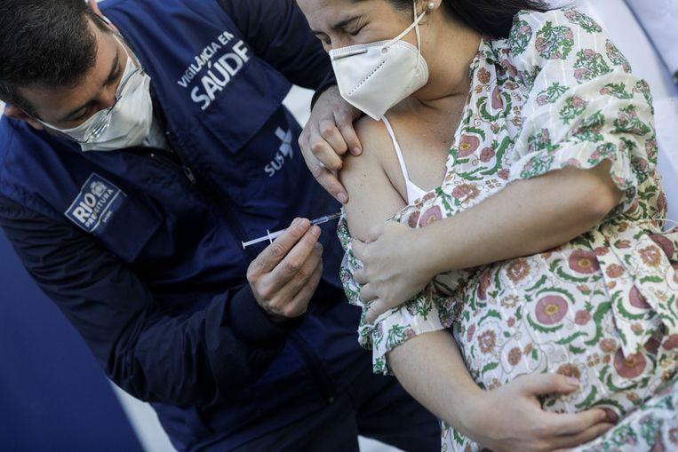 Een zwangere vrouw wordt in Rio de Janeiro ingeënt tegen het coronavirus. Beeld REUTERS