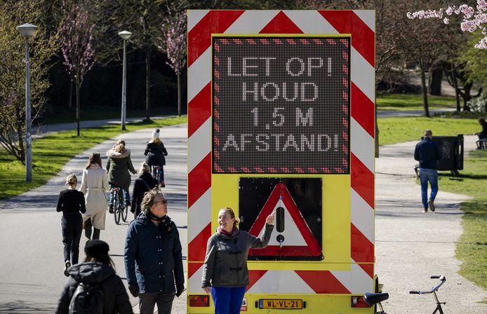 Een bord waarschuwde vorig jaar in het Vondelpark om 1,5 meter afstand te houden van elkaar vanwege het coronavirus.