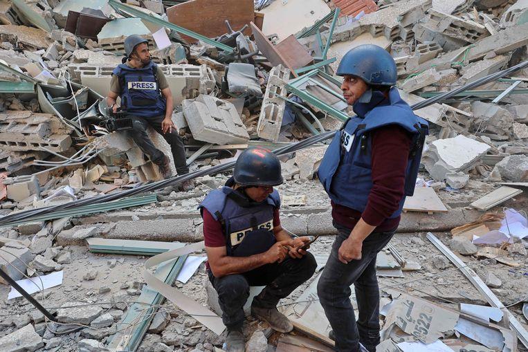 Journalisten op de puinhoop van de Jala Tower in de Gazastrook, waar internationale media-organisaties kantoor hielden. De toren werd door een Israëlische luchtaanval met de grond gelijk gemaakt. Beeld AFP