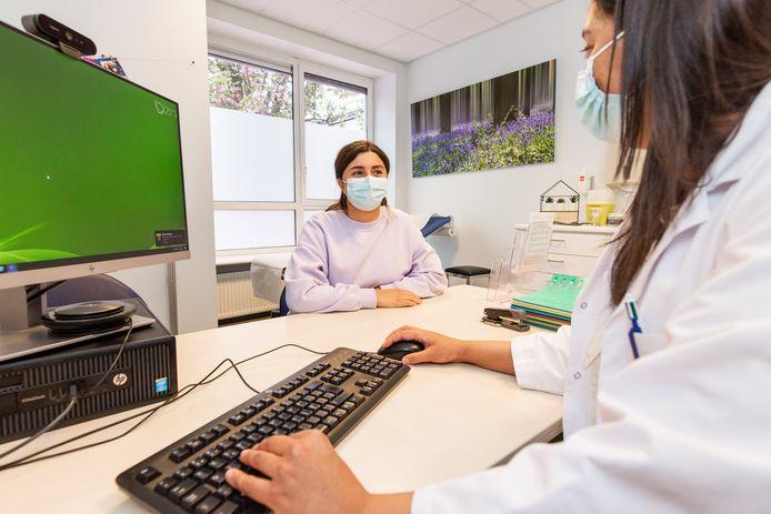 Een warmer ingericht dokterskabinet, met o.a. foto's en planten.