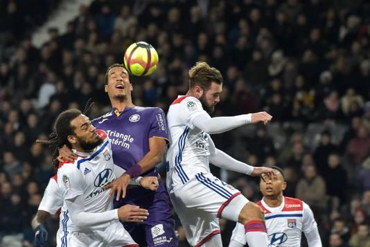 Toulouse-verdediger Christopher Jullien wint in de lucht van Jason Denayer en Lucas Tousart van Olympique Lyon. Rechts Kenny Tete.
