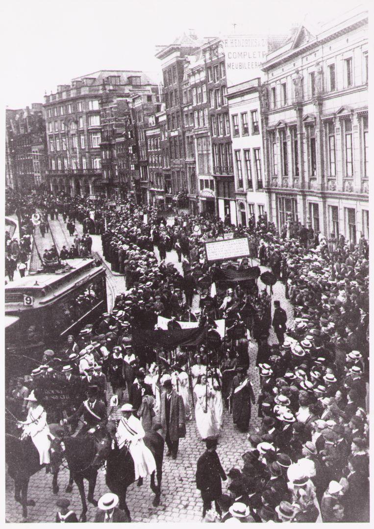 Amsterdam 18 juni 1916. Rond de 18.000 vrouwen en mannen demonstreren voor het vrouwenkiesrecht. Suffragettes dragen hier wit met een groen/paarse sjerp over hun kleding. Beeld