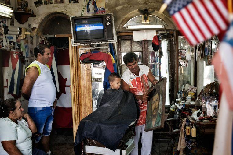 Een kapper in Regla, een voorstad van Havana, maakt even tijd om het stof van een portret van Che Guevara te borstelen. Beeld © YURI KOZYREV / NOOR