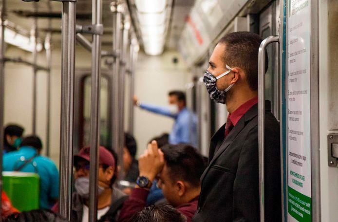 Een man draagt een mondkapje in de metro van Mexico City. Het OMT onderzoekt of dat in Nederland ook nut heeft.