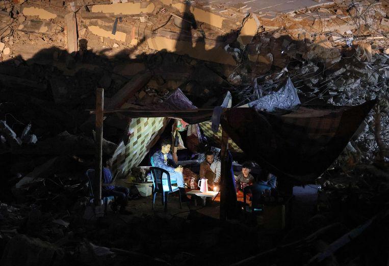In Gaza-stad zitten Palestijnen bij elkaar in een zelfgemaakte tent op de ruïnes van een gebouw dat verwoest werd door Israëlische luchtaanvallen. Het staakt-het-vuren tussen Israël en de Palestijnse gebieden lijkt nu stand te houden. Beeld AFP