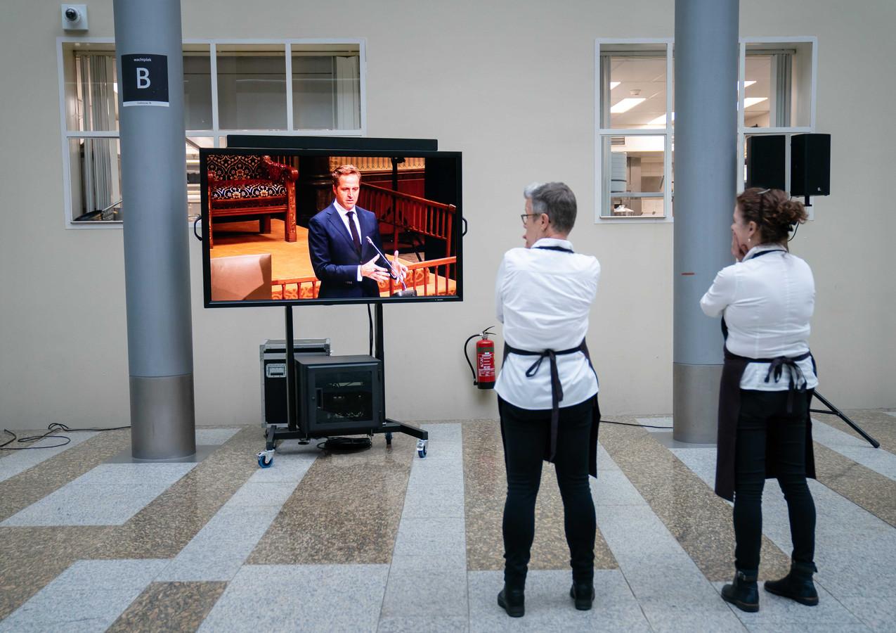Medewerkers van de Tweede Kamer kijken naar demissionair Minister Hugo de Jonge van Volksgezondheid, Welzijn en Sport (CDA) tijdens een debat over het coronavirus.