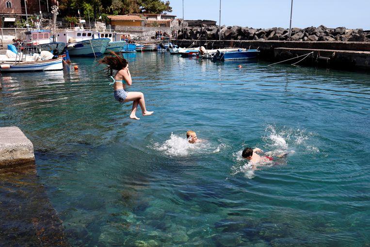 In San Giovanni li Cuti, in het oosten van Sicilië, genieten kinderen maandag van het moment van vrijheid dat ze na bijna twee manden weer hebben.   Beeld Antonio ParrinelloREUTERS